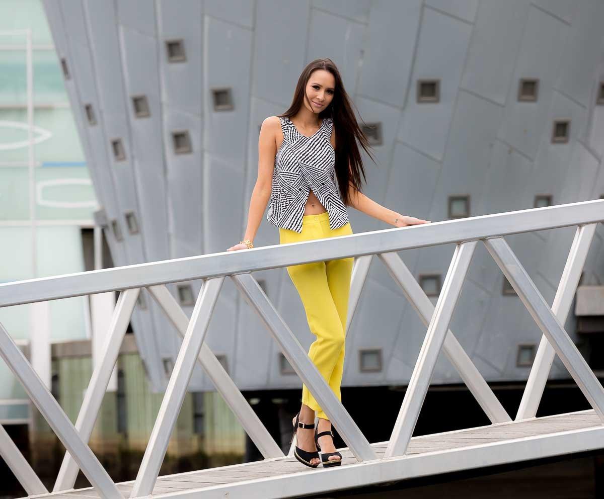 Model on bridge wearing yellow pants