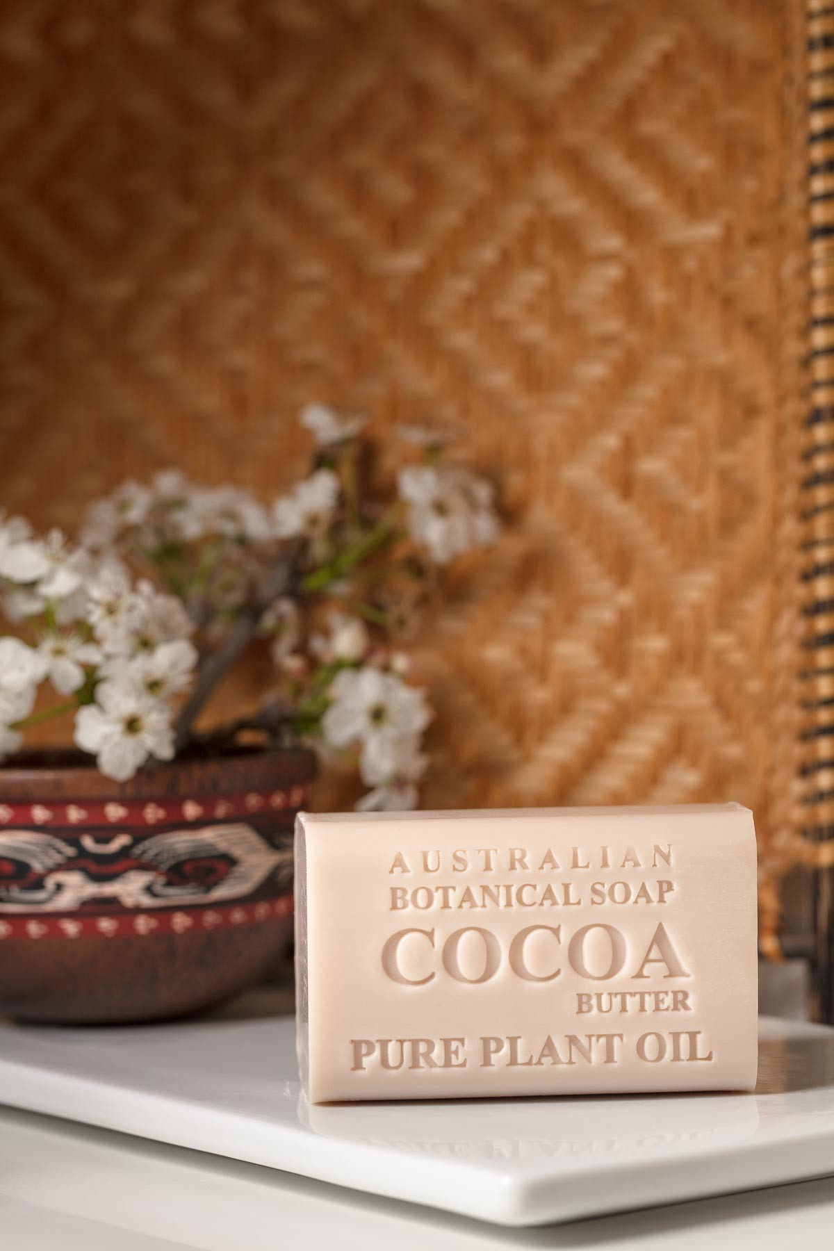 Australian Botanic Soap Cocoa dry vertical over soap dish and rustic background - Lifestyle advertising product photo