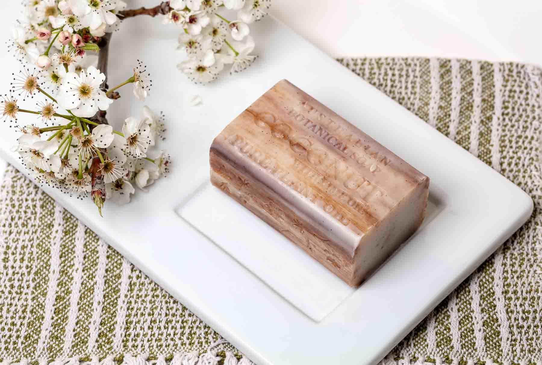 Australian Botanic Soap coconut dry on soap dish top side view with flowers - Lifestyle advertising product photo