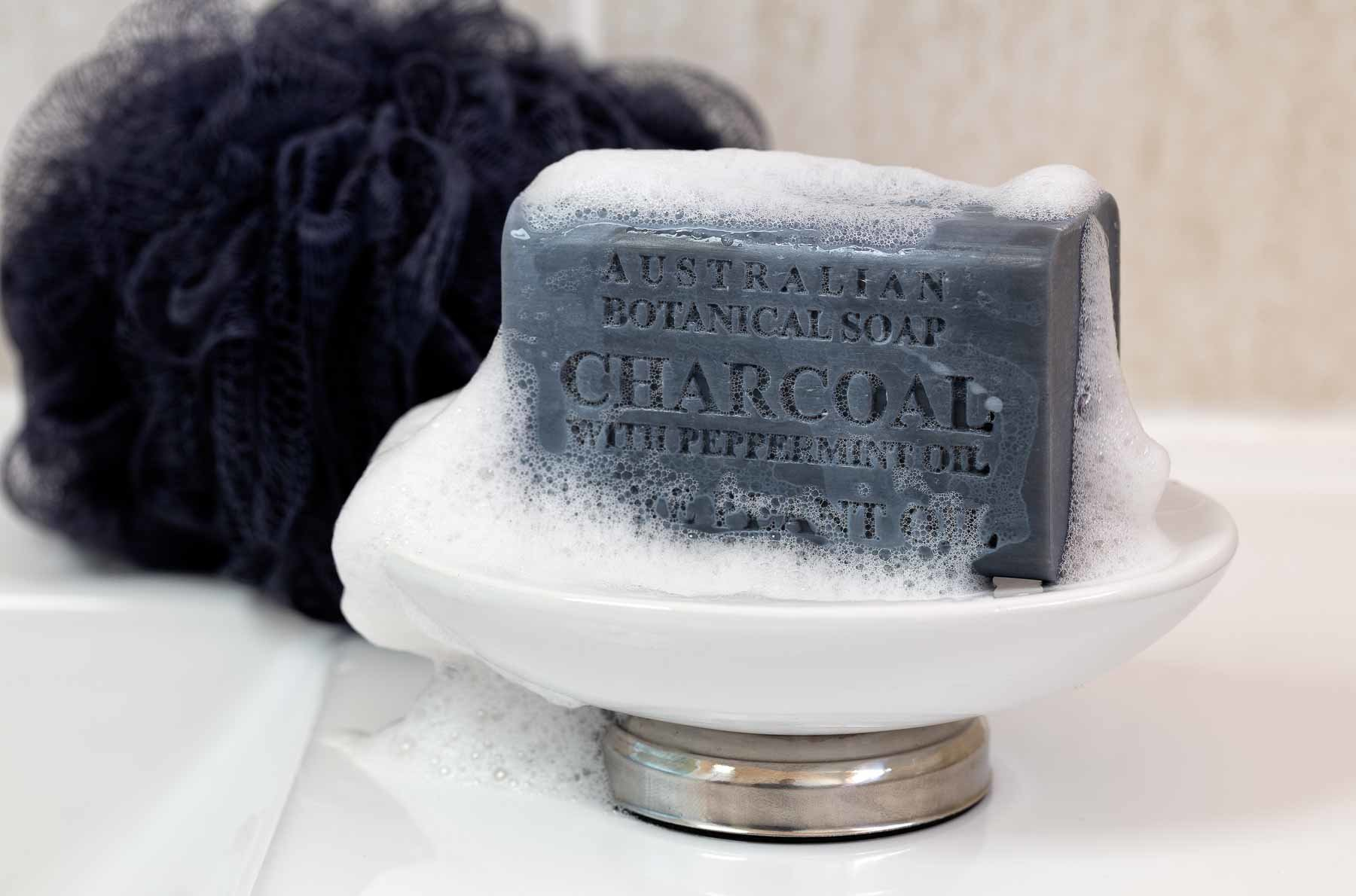 Australian Botanical Soap charcoal wet vertical over soap dish - Lifestyle advertising product photo