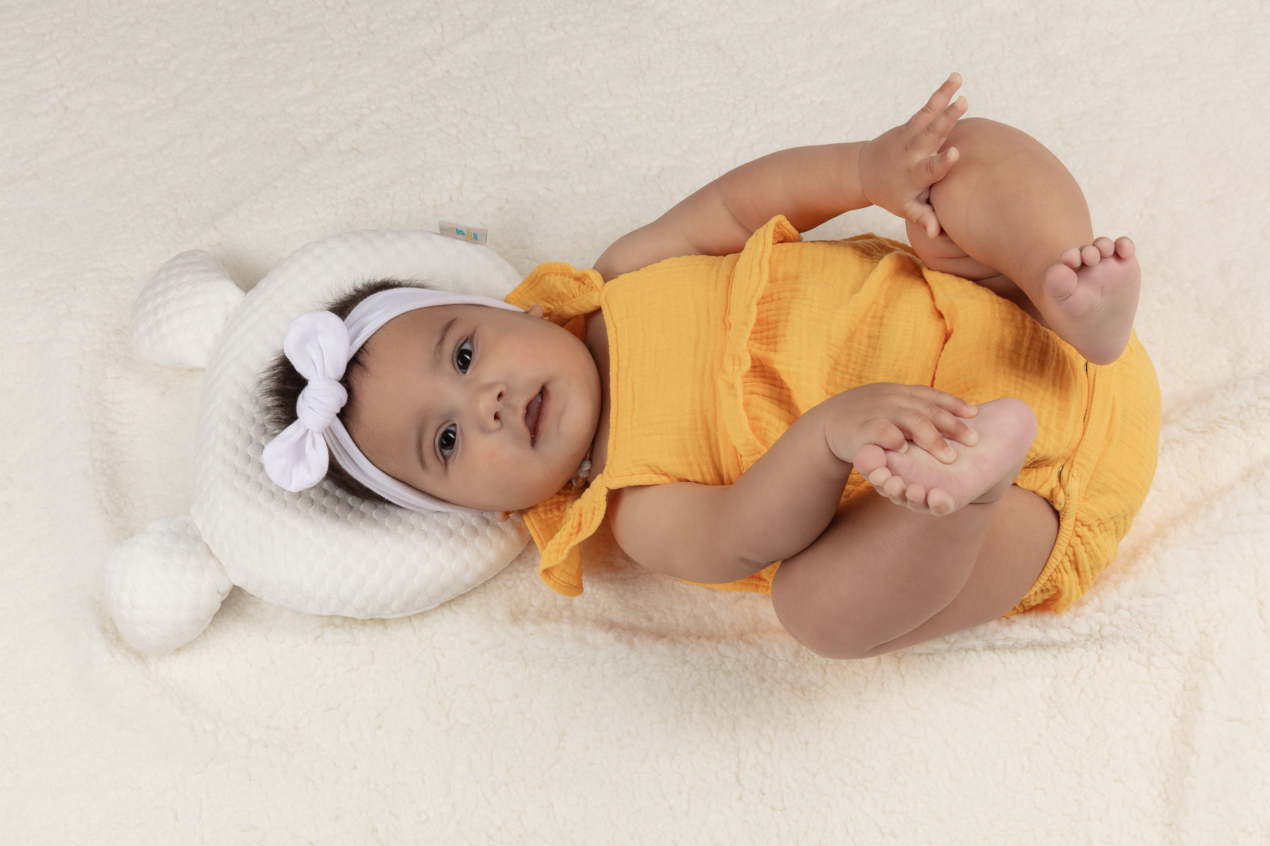Baby Pillow with baby full body holding feet_- Advertising product photography for Amazon