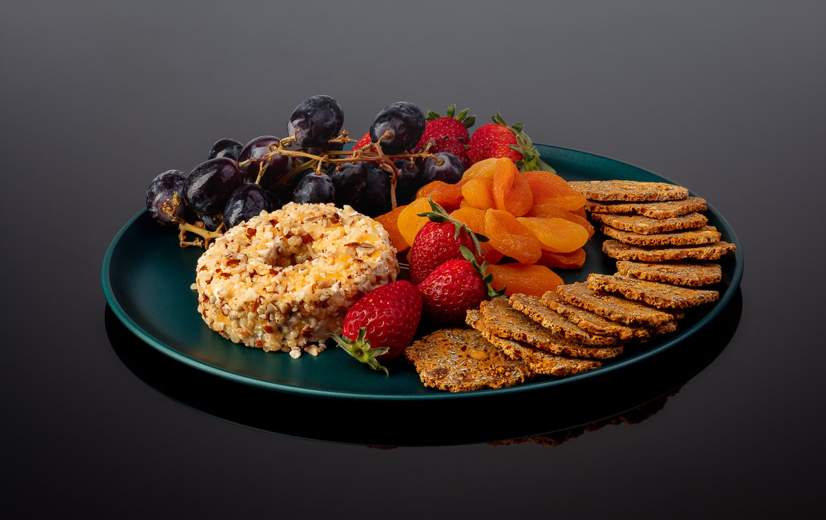 Defrost plate with cheese and fruits on black