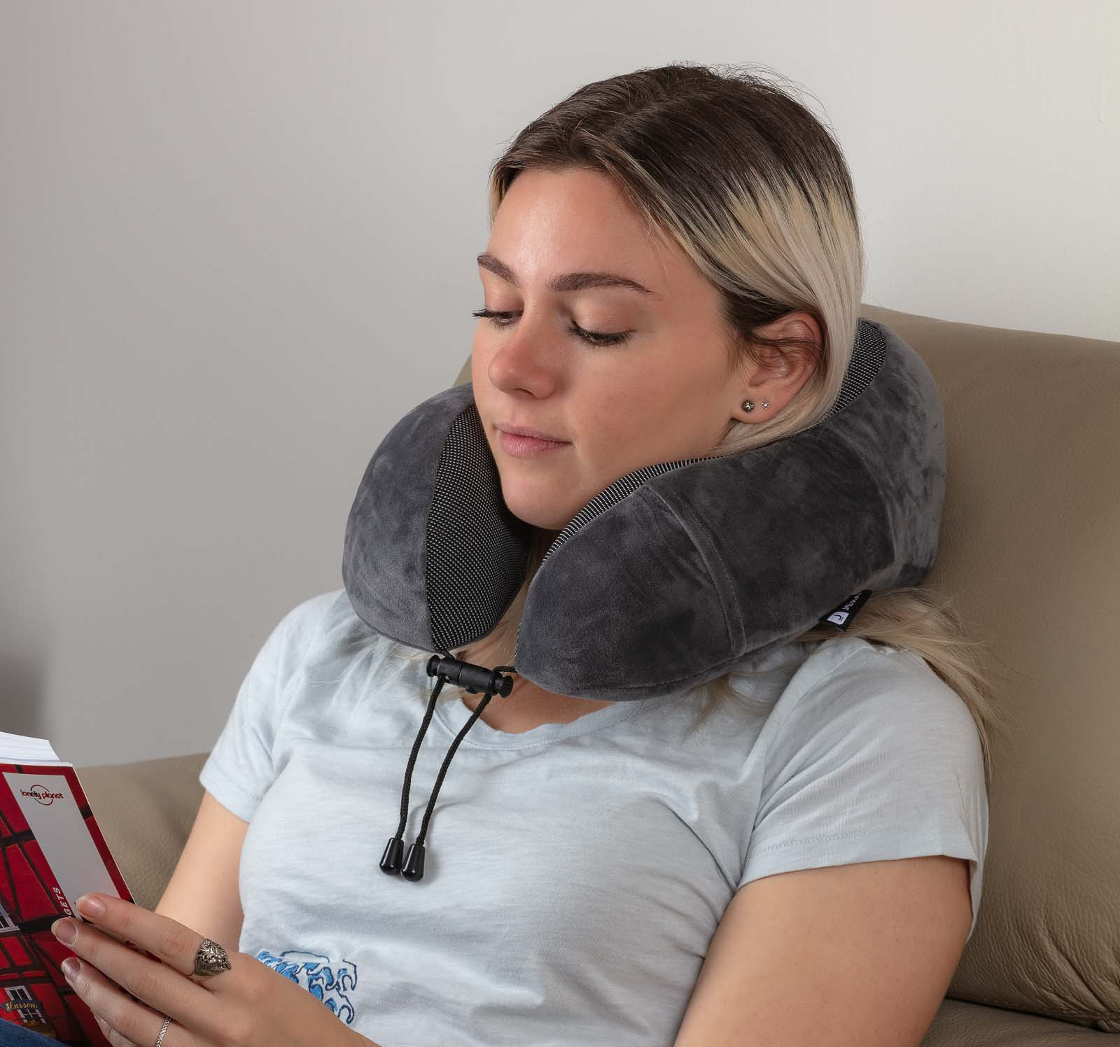 Jera Travel Pillow Product in use by model while reading book - Lifestyle amazon product photography sample
