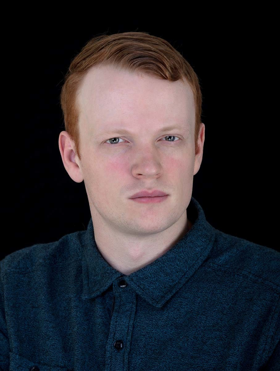 jonathan Simpson actor professional profile with a stong masculine look and black backgroiund